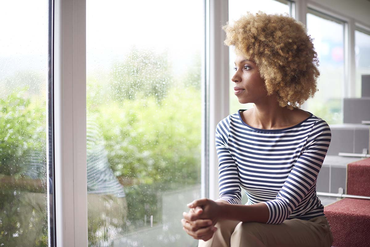 woman looking out winder thinking about risk factors for addiction
